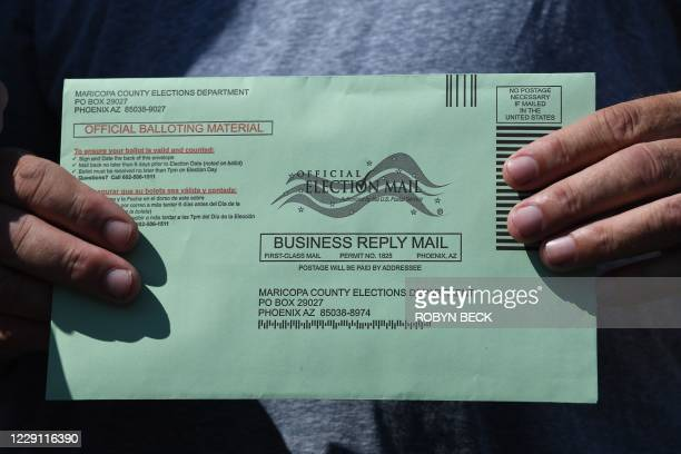 Voter displays their mail-in ballot envelope as they arrive to cast their ballot in the US presidential election at an early voting location in...