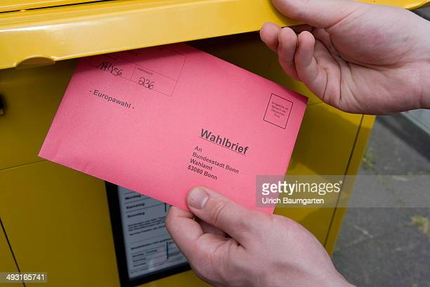 Voter drops a ballot envelope for the 2014 European elections into a mailbox on May 22 2014 in Bonn Germany