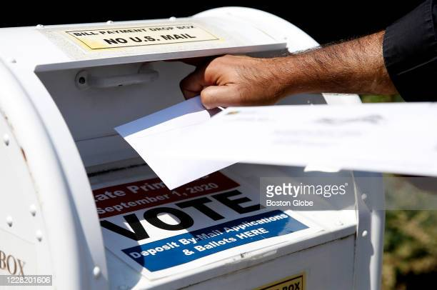Voter drops a ballot into the box for mail-in ballots outside of Newton City Hall in Newton, MA on Aug. 23 where there's a crowded field in the...