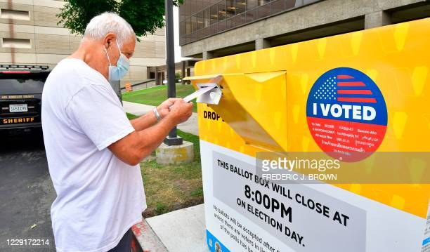 Voter drops his ballot for the 2020 US elections into an official ballot drop box at the Los Angeles County Registrar in Norwalk, California on...