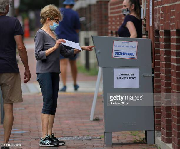 Voter drops off a mail-in ballot in a collection box outside the Cambridge City Hall Annex at the corner of Broadway and Inman Street in Cambridge,...