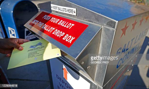 Voter drops off his mail in ballot at a dropbox at the Salt Lake County election office in Salt Lake City, Utah, on October 29, 2020.
