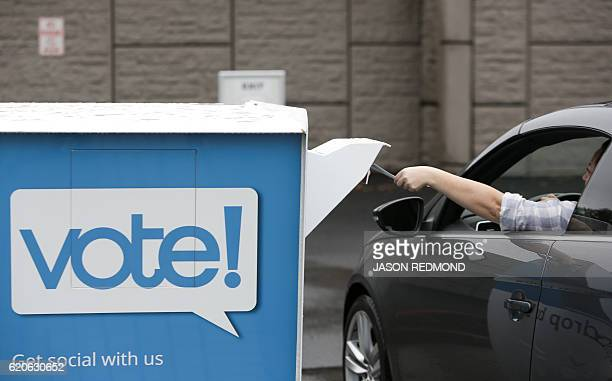 A voter drops off their mailin ballot at the King County County Department of Elections in Renton Washington on November 2 2016 Washington Oregon and...
