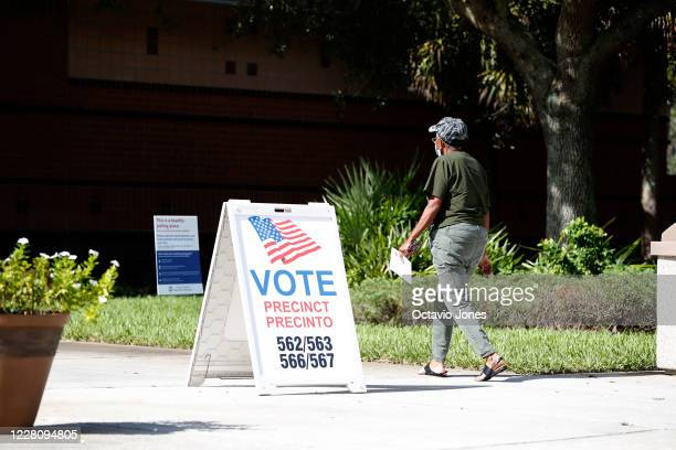 A voter enters a polling precinct to cast their ballot in Florida's primary election on August 18 2020 in Tampa Florida Florida joins Alaska and...