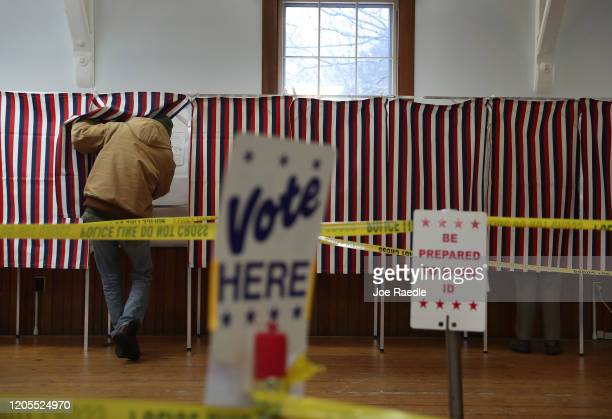 A voter enters a voting booth setup in a polling station at the Town Hall on February 11 2020 in Chichester New Hampshire Voters are casting their...