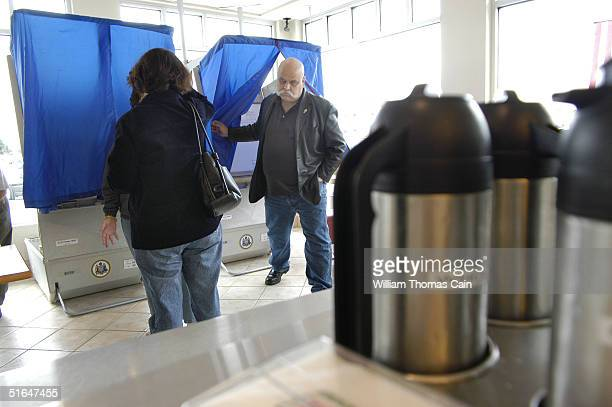 A voter exits a voting booth at a Krispy Kreme Donuts shop which is a polling place November 2 2004 in Philadelphia Pennsylvania Pennsylvania one of...