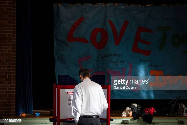 A voter fills in their ballot with their choice in the Democratic presidential primary elections at the Taylor Elementary School polling location on...