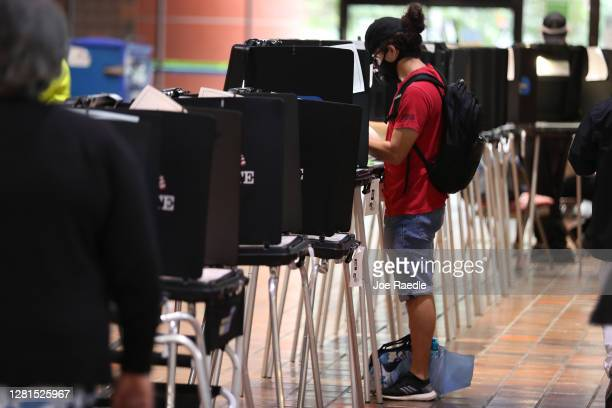 A voter fills out his ballot as he votes at the Stephen P Clark Government Center polling station on October 21 2020 in Miami Florida The state of...