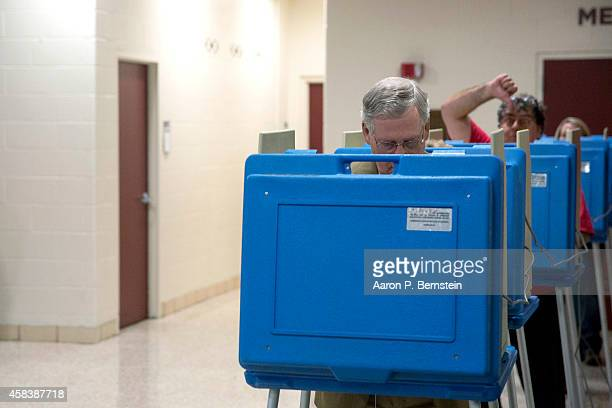 A voter gestures as Senate Minority Leader US Sen Mitch McConnell votes in the midterm elections at Bellarmine University November 4 2014 in...