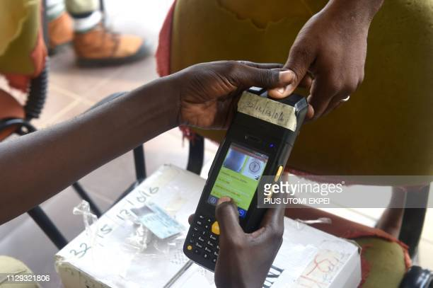 A voter has her thumbprint taken alongside her Permanent Voters Card at a polling station in Port Harcourt Rivers State on March 9 during voting to...