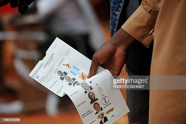 A voter holds a ballot while waiting in line at a polling station in Uganda's capital Kampala on February 18 2011 to vote in presidential and...
