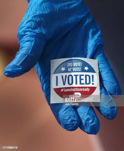 Voter holds an, 'I Voted!', sticker after wearing a glove as she cast her ballot during the Florida presidential primary as the coronavirus pandemic...