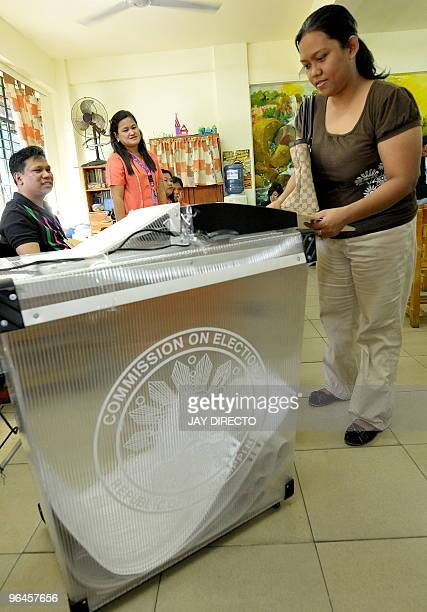 A voter in Quezon City in suburban Manila feeds her ballots in to a automated counting machine during a mock election intended to test the automated...