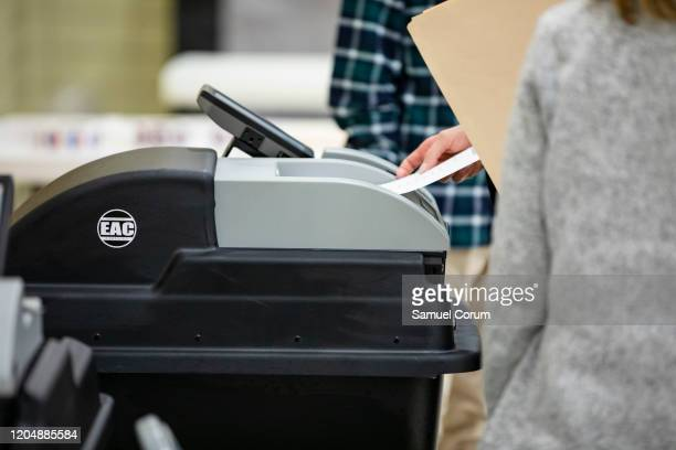 A voter inserts her ballot for the Democratic presidential primary into a voting machine at the Madison Community Center polling place on Super...