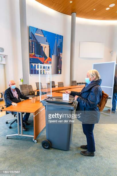 Voter inserts her ballot paper in the ballot box at the polling station inside the Kampen town hall for the general elections for theHouse of...