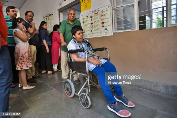 A voter is being assisted on a wheelchair as she exits after casting her vote at a polling booth in Model town on May 12 2019 in New Delhi India...