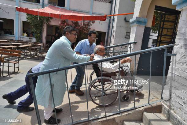 A voter is being assisted on a wheelchair at a polling booth in Model town on May 12 2019 in New Delhi India Voting began for the 59 seats in the 6th...