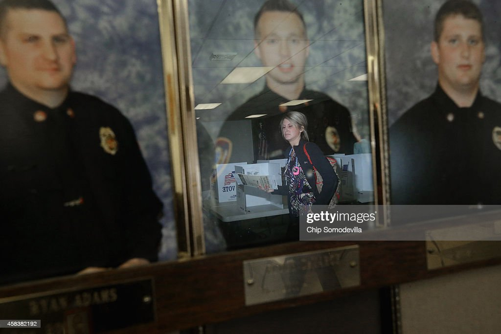 A voter is reflected in photographs of Red Oak, Iowa, firefighters as she casts her ballot on election day at the Red Oak Fire Department November 4, 2014 in Red Oak, Iowa. According to the polls, Republican U.S. Senate candidate Joni Ernst is in a neck-and-neck race with Democratic candidate Rep. Bruce Braley (D-IA), and the election in Iowa could decide which party controls the U.S. Senate.