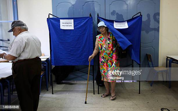 A voter leaves a booth after marking her ballot paper ahead of casting her vote in the second round of the Greek general elections at a polling...