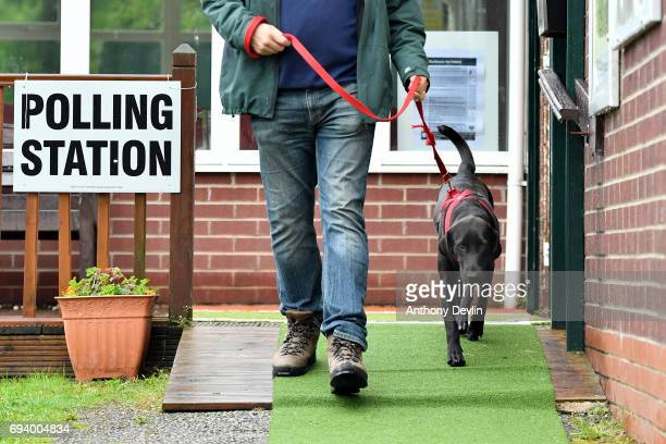 A voter leaves a polling station with Guia a Labrador rescued from Ecuador after casting his vote in Stalybridge on June 8 2017 in Greater Manchester...
