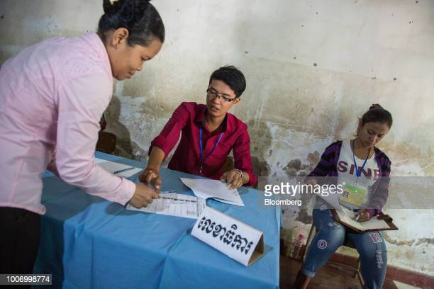 A voter left registers before casting her ballot for the general election at a polling station in Phnom Penh Cambodia on Sunday July 29 2018 As...