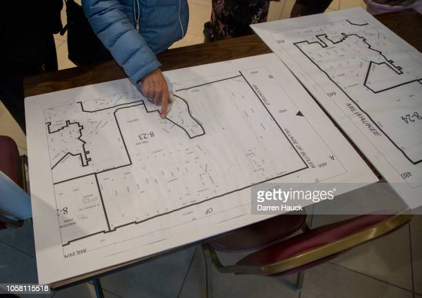 A voter looks at a map while waiting to cast a midterm ballot on November 6 2018 in Wauwatosa Wisconsin Voters are turning out in historic numbers to...