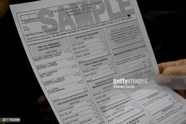 A voter looks at a sample ballot as he waits in line at a polling location on November 8 2016 Kansas City Missouri Americans will choose between...