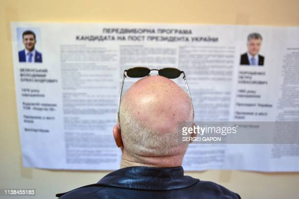 A voter looks at an information placard bearing portraits of the both candidates President Petro Poroshenko and comedian Volodymyr Zelensky at a...