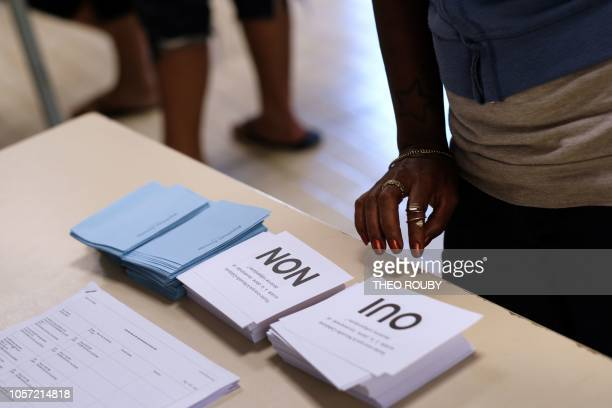A voter looks at ballot papers as people arrive to vote in the referendum on New Caledonia's independence from France in Noumea on the French...
