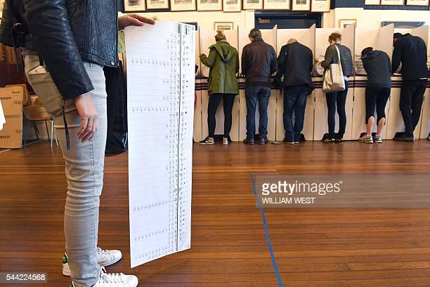 A voter looks at the ballot paper at a voting station in the Sydney suburb of Bondi Beach on July 2 2016 Australians flocked to vote in the national...