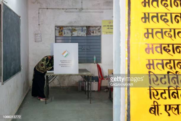 A voter marks her ballot at a polling booth for India's Madhya Pradesh state assembly election in Bhopal on November 28 2018 Millions of Indians...