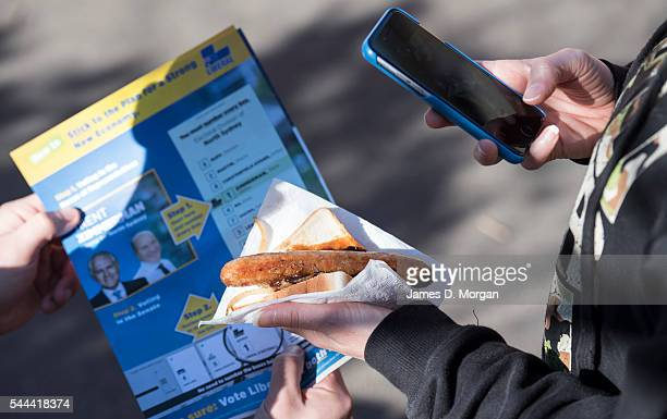 A voter photographs his sausage sizzle sandwich on July 2 2016 in Sydney Australia Sausage sizzles have over time become an Australian tradition on...