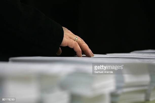 A voter picks up a ballot paper at a polling station during the Spanish general election on March 9 2008 in Madrid Spain Spaniards are flocking to...
