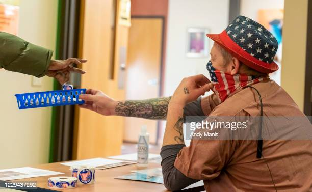Voter picks up a sticker from poll worker MacGregor Wale after voting at the Catholic Multicultural Center on November 3, 2020 in Madison, Wisconsin....
