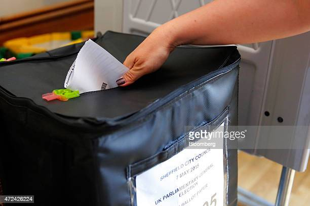 A voter places her vote into a Sheffield City Council ballot box in a polling station located inside the Bank View cafe as voting continues in the...