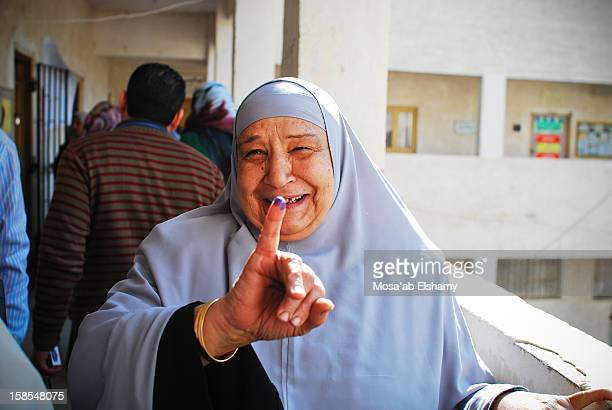 CONTENT] A voter poses her inked finger outside of a polling station in Damanhour town the captial of Behira during the parlimentary elections
