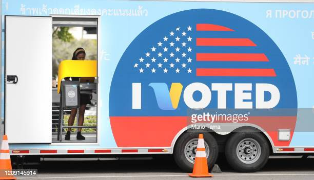 A voter prepares her ballot during early voting for the California presidential primary election at a new LA County 'Mobile Vote Center' outside...