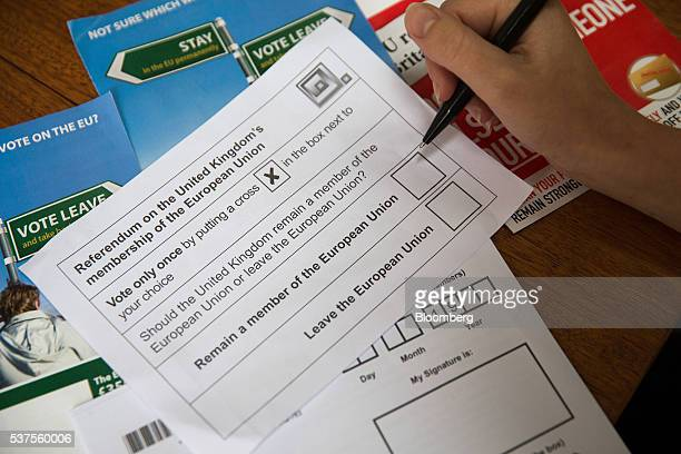 A voter prepares to mark a European Union referendum postal ballot slip with choices to remain in or to leave the European Union in this arranged...