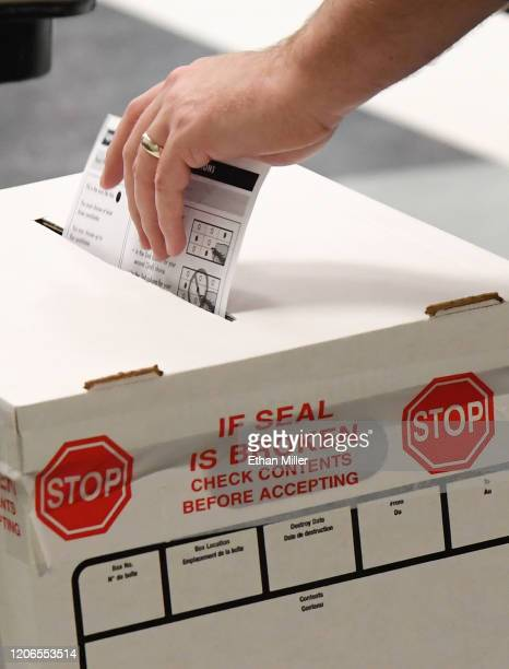 A voter puts a ballot in a ballot box while voting on the first day of early voting for the upcoming Nevada Democratic presidential caucus at the...