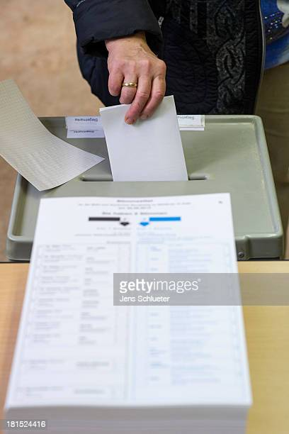 A voter puts his ballot in a ballot box at a primary school on September 22 2013 in Halle Germany Germany is holding federal elections that will...