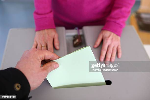 A voter puts his ballot in the voting box in BadenWuerttemberg state elections on March 13 2016 in Stuttgart Germany State elections taking place...