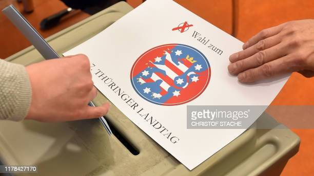 A voter puts into a ballot box her ballot papers for Thuringian state elections on October 27 2019 at a polling station in Erfurt eastern Germany