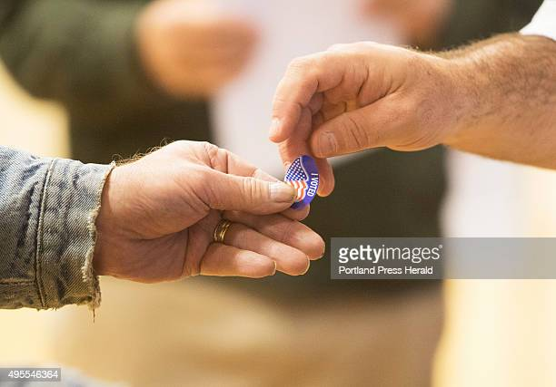 A voter receives an 'I Voted' sticker at the Reiche School in Portland