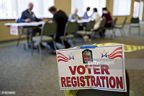 A Voter Registration sign hangs near a table where residents fill out paperwork at a polling location during the presidential primary vote in...