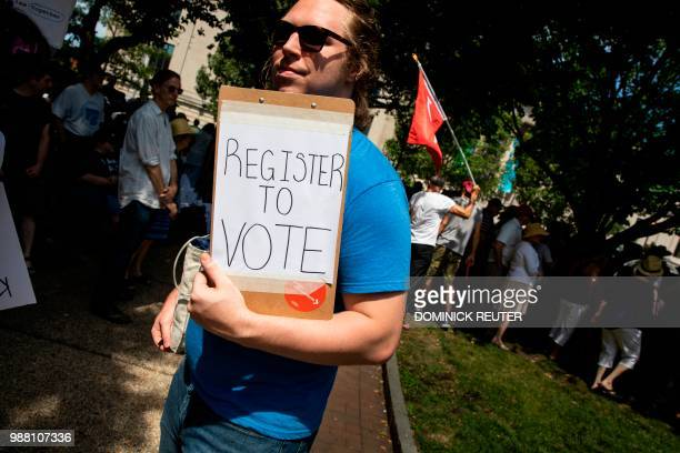 A voter registration volunteer works at a rally against US President Donald Trump's immigrant family separation policies in Philadelphia Pennsylvania...