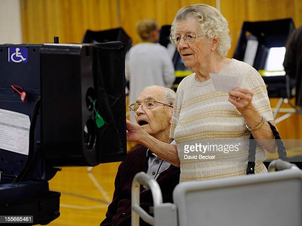Voter Robert Krack casts his ballot with the help of Pauline Vallee at the polling station at John Fremont Middle School on November 6 2012 in Las...