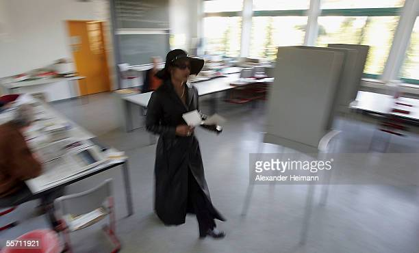 A voter rushes into a polling booth in a polling station to vote in the German Bundestag elections on September 18 2005 in Gross Gerau Germany