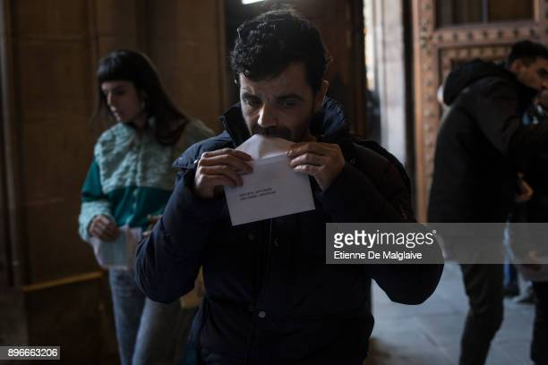 A voter seals the envelope containing his ballot at a polling station inside the hall of the University of Barcelona on December 21 2017 in Barcelona...