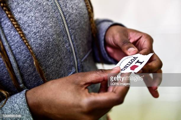A voter seen holding a sticker with the words I love voting at the Barrack Recreation Centre in Down town Columbus during the primary elections...
