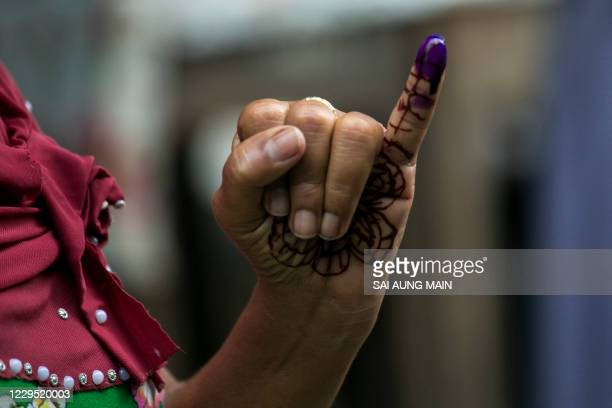 Voter shows an ink-marked finger after casting her ballot at a polling station in Yangon on November 8, 2020.